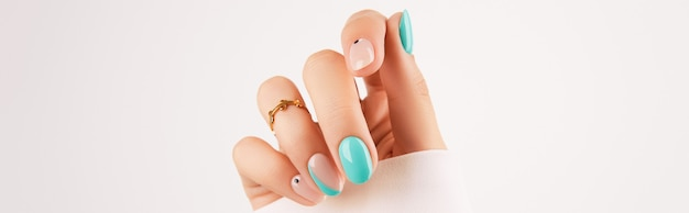 Mão da mulher com manicure turquesa da moda com espaço de cópia