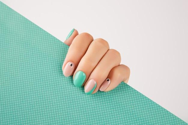 Mão da mulher com manicure turquesa na moda com espaço de cópia. tendências de design de manicure de verão. conceito de moda beleza