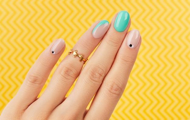 Mão da mulher com manicure turquesa na moda em fundo amarelo. tendências de design de manicure de verão.