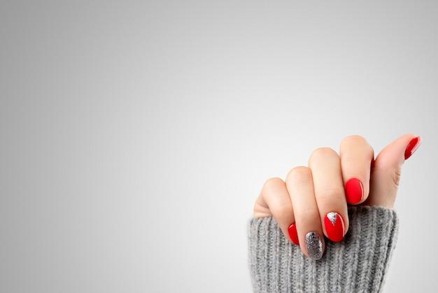Mão da mulher com manicure vermelha na moda. desenho de unhas de natal de ano novo