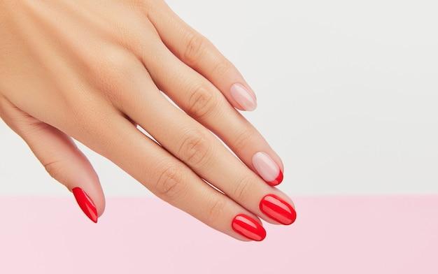 Mão da mulher com manicure vermelha na moda sobre fundo branco e rosa