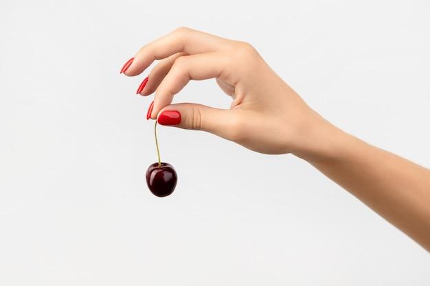 Mão da mulher com manicure vermelha segurando cereja