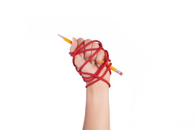 Mão da mulher com o lápis amarelo amarrado com corda vermelha, liberdade do conceito da imprensa.