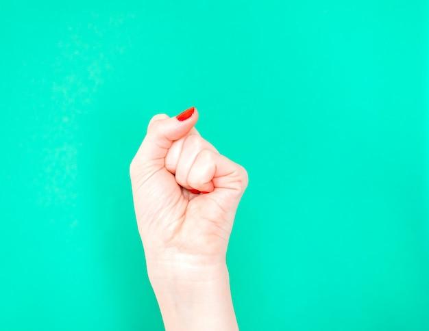 Mão da mulher com o punho apertado no fundo isolado da cor verde de turquesa.