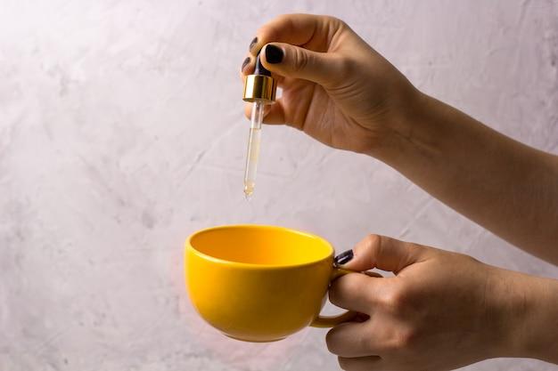 Mão da mulher com pipeta e caneca. vitaminas líquidas