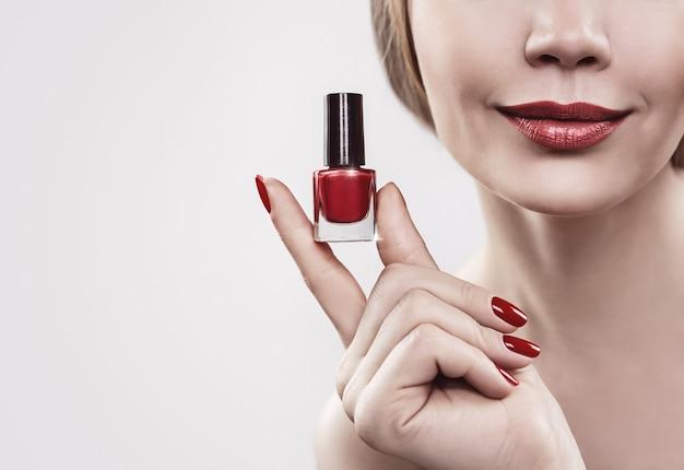 Mão da mulher com um frasco de esmalte vermelho isolado na parede branca