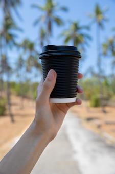 Mão da mulher com uma xícara de papel cartão de chá de café pelo parque com palmeira