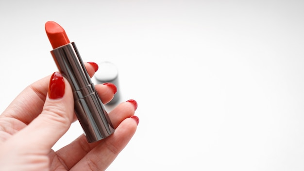 Mão da mulher com unhas vermelhas, segurando batom vermelho. close-up da mão feminina na superfície branca
