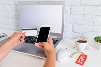 Mão da mulher, compras on-line através do telefone móvel sobre o laptop