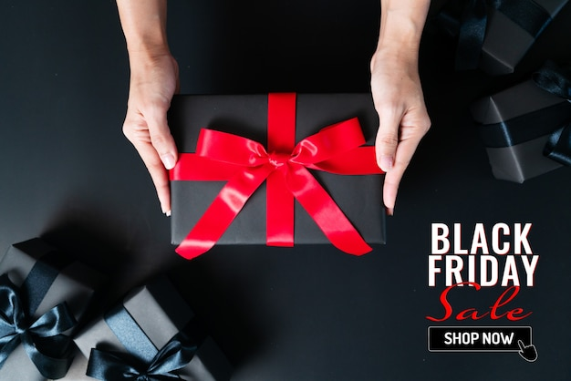 Mão da mulher dá a caixa de presente preta em fundo preto
