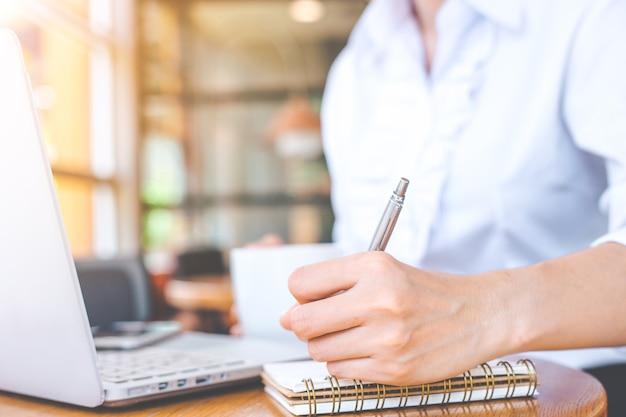 Mão da mulher de negócio usando o portátil e escrevendo no bloco de notas com uma pena.