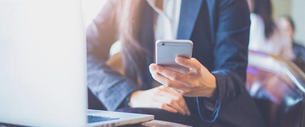 Mão da mulher de negócio usando o telefone móvel no escritório. bandeira de web.