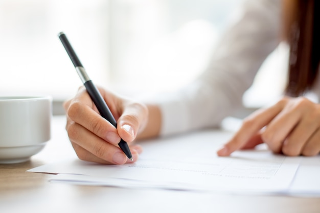 Mão da mulher de negócios escrito em papel no escritório
