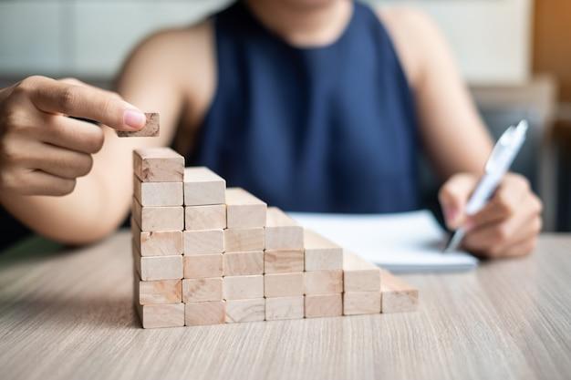 Mão da mulher de negócios que coloca ou que puxa o bloco de madeira no edifício.