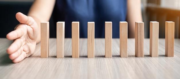 Mão da mulher de negócios que para os dominós de madeira de queda.