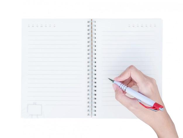 Mão da mulher do close up que escreve no livro de nota com linha na vista superior isolada no fundo branco