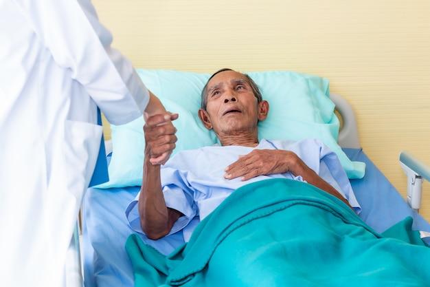 Mão da mulher do médico que tranquiliza e que discute o homem paciente sênior na sala de hospital.