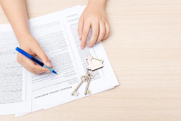 Mão da mulher e tecla home. contrato assinado e chaves da propriedade com documentos