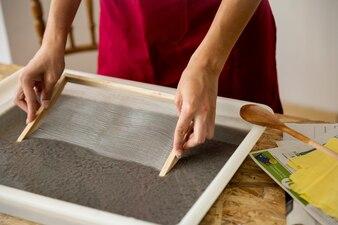Mão da mulher embebendo o molde na polpa de papel