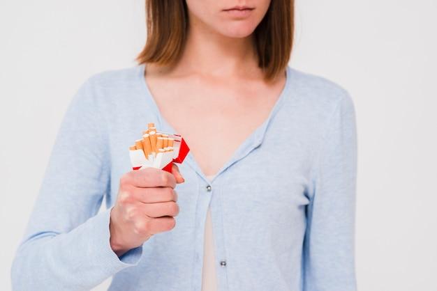 Mão da mulher, esmagando o pacote de cigarro