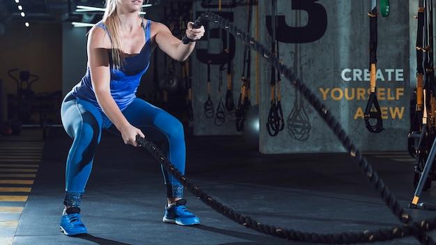 Mão da mulher, exercitando com cordas de batalha no ginásio