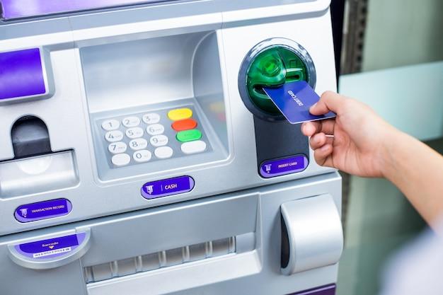 Mão da mulher, inserindo o cartão de débito em uma máquina atm