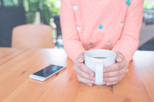 Mão da mulher na camisola morna que prende uma chávena de café.