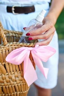 Mão da mulher na moda com saco de palha com desinfecção mãos gel na bolsa.