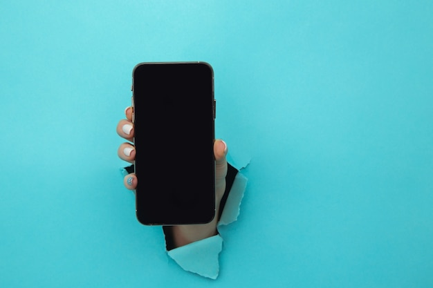 Mão da mulher no buraco do papel segurando o smartphone.