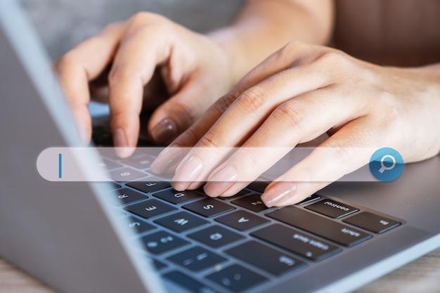 Mão da mulher no teclado do notebook procurando emprego