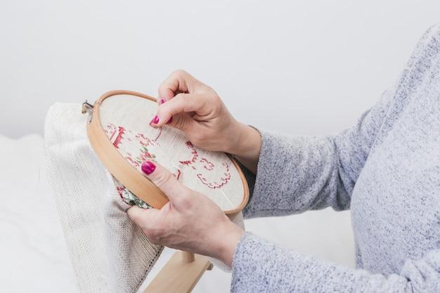 Mão da mulher padrão de costura cruz em um aro contra um fundo branco