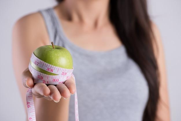 Mão da mulher que guarda a fita de medição em torno da maçã verde fresca.
