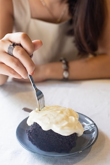 Mão da mulher que guarda a forquilha que corta o bolo de chocolate escuro com queijo creme no café.
