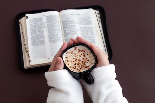 Mão da mulher que guarda a xícara de café e que lê a bíblia sagrada.