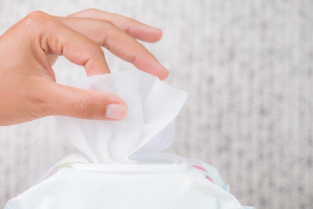 Mão da mulher que guarda limpezas molhadas do pacote. conceito de saúde.