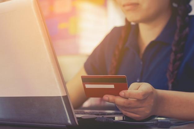 Mão da mulher que guarda o cartão de crédito e que usa o laptop.