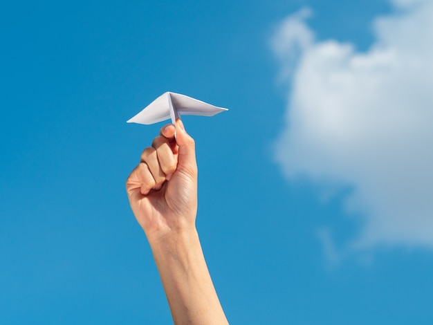 Mão da mulher que guarda o foguete de papel com fundo do céu azul. conceito de liberdade