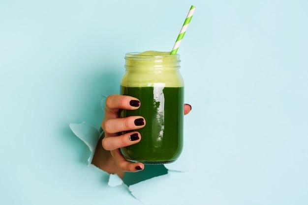 Mão da mulher que guarda o frasco de vidro do batido verde, suco fresco contra o fundo azul.