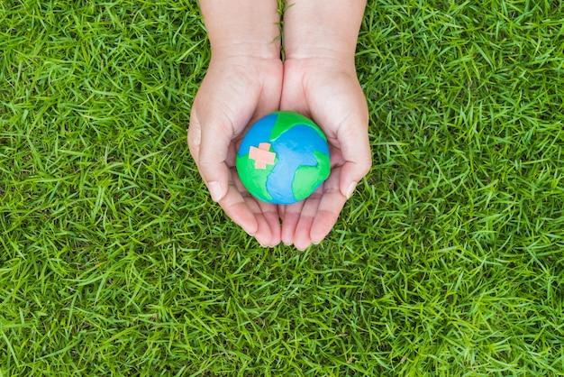 Mão da mulher que guarda o globo feito a mão no fundo do campo de grama verde.