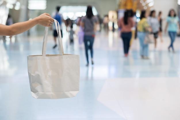 Mão da mulher que guarda o saco de compras de eco na loja com espaço da cópia para o texto. proteção ambiental, zero desperdício, reutilizável, não diga plástico, dia mundial do meio ambiente e conceito do dia da terra