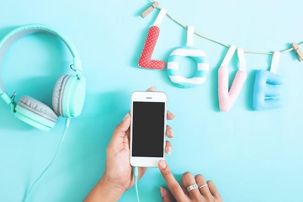 Mão da mulher que guarda o telefone celular com a tela vazia no fundo da cor. conceito de amor