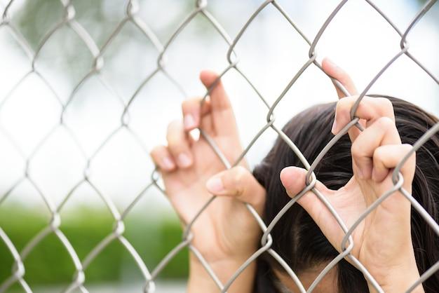 Mão da mulher que guarda sobre a cerca do elo de corrente para a liberdade.
