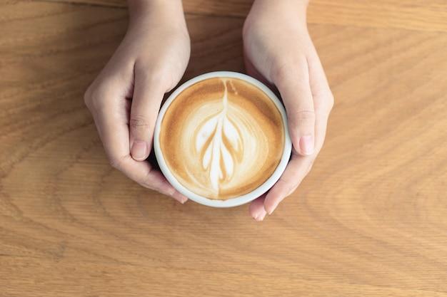 Mão da mulher que guarda uma caneca de café branco. o café é um latte. mesa na madeira