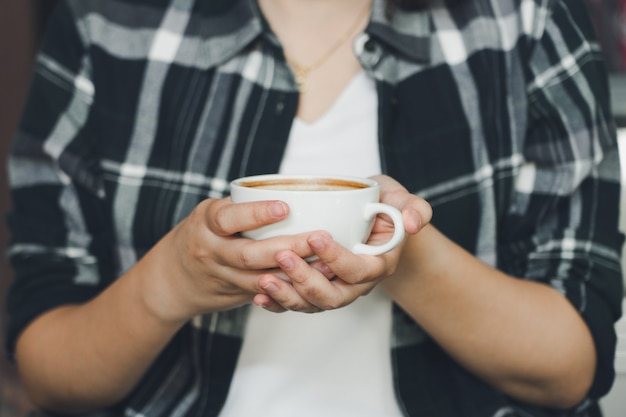 Mão da mulher que guarda uma caneca de café branco. o café é um latte.