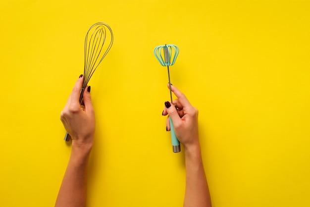 Mão da mulher que guarda utensílios da cozinha no fundo amarelo.