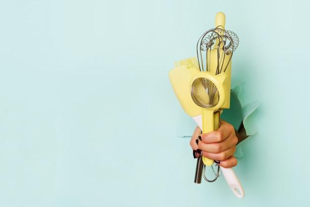 Mão da mulher que guarda utensílios da cozinha no fundo azul.