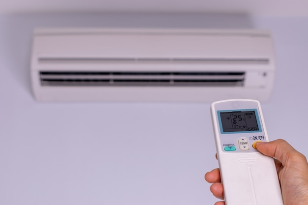Mão da mulher que liga o condicionador de ar. conceito de economia de energia.