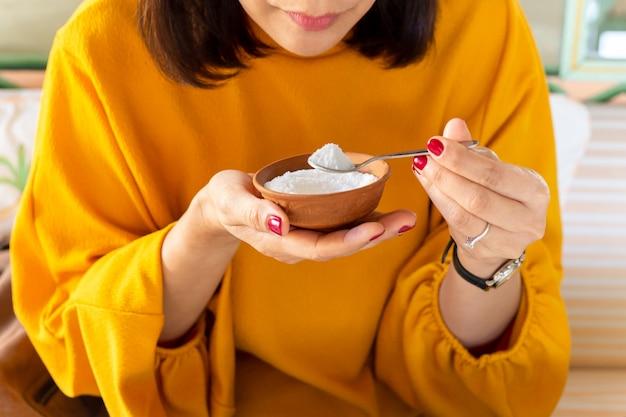 Mão da mulher que mantém a colher completa do conceito dos cuidados médicos do açúcar.