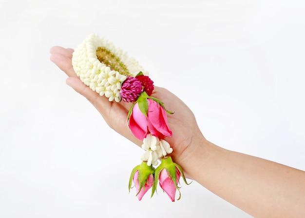 Mão da mulher que mantém a festão tailandesa para o respeito isolada no fundo branco.