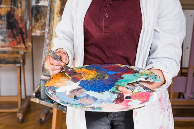 Mão da mulher que mistura a cor da pintura de óleo na paleta na oficina